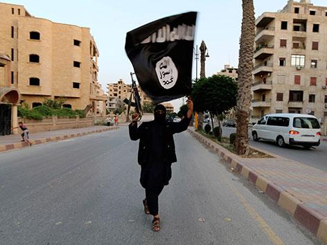 Ein ISIS-Kämpfer mit der Flagge des Islamischen Staates in der menschenleeren Stadt Kufa