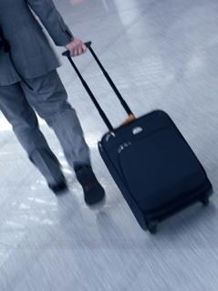 Ein Mann zieht einen Koffer auf Rollen hinter sich her