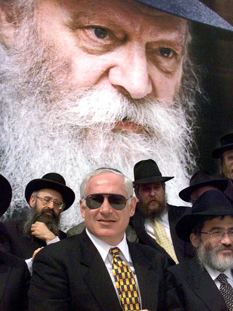 Israels Premier Benjamin Netanjahu sitzt anlässlich einer Bar-Mizwa-Feier vor einem überlebensgroßen Plakat von Rabbi Schneerson