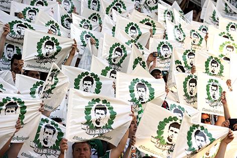 """Rapid-Fans halten Plakate mit Porträt von Gerhard Hanappi und Aufschrift """"1977-2014"""""""
