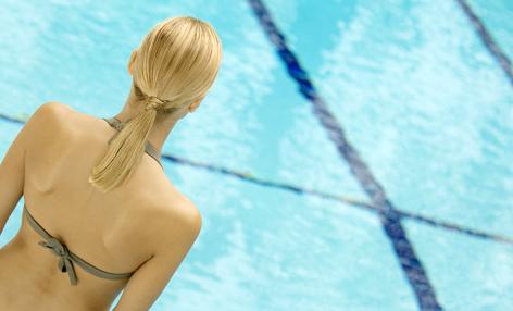 Eine Frau schaut auf einen Pool