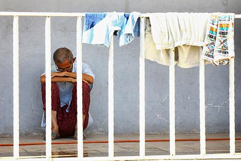 Mann in verzweifelter Pose auf Balkon