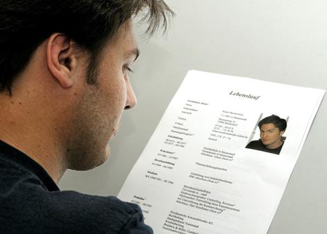 Ein junger Mann hat für eine schriftliche Bewerbung einen Lebenslauf mit eingefügtem Foto erstellt.