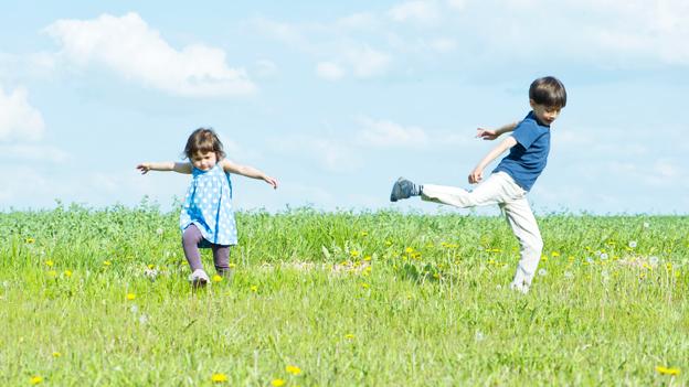 Zwei Kinder laufen über eine Wiese