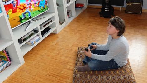 Bub sitzt vor einem Fernseher und spielt ein Game