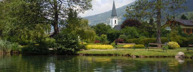 Seepark am Ufer des spiegelnden Brennsees mit der Kirche von Feld am See