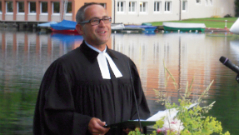 Pfarrer Michael Guttner im Talar am See