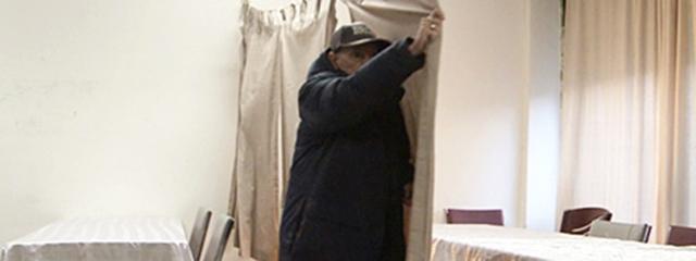 Alter Mann zieht Vorhang durch einen Raum