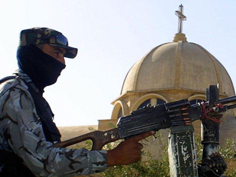 Ein bewaffneter Mann vor einer Kirche in Mussul