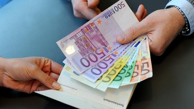 Ein Sparbuch und Geldscheine in einem Geldinstitut
