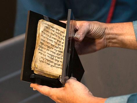 Hände halten ein 1.200 Jahre altes jüdisches Gebetbuch (Siddur)