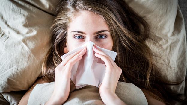 Eine Frau liegt im Bett und putzt sich die Nase