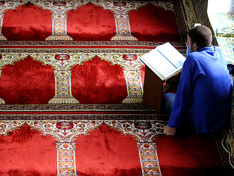 Muslim liest auf Gebetsteppich im Koran