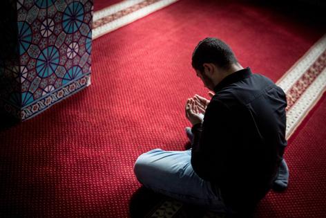 Ein betender Muslim auf rotem Teppichboden