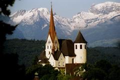 die Basilika Rankweil mit ihren spitzen Türmen und der runden Ausbuchtung hoch erhoben inmitten schneebedeckter Berge