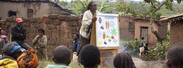 schwarze Helferin erklärend an einer Bildtafel im Hof vor halbwüchsigen schwarzen Schülern