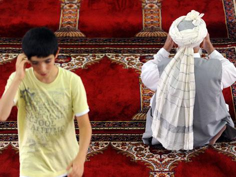 Ein älterer Muslim auf einem Gebetsteppich, ein Bub daneben