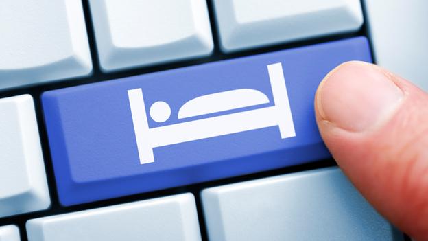 Finger auf Computertaste mit Bettensymbol