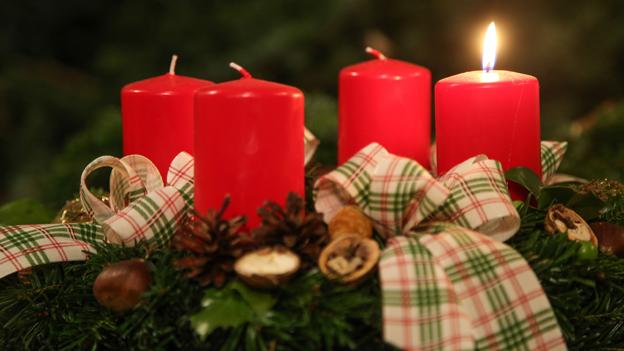 Auf einem Adventkranz brennt die erste Kerze