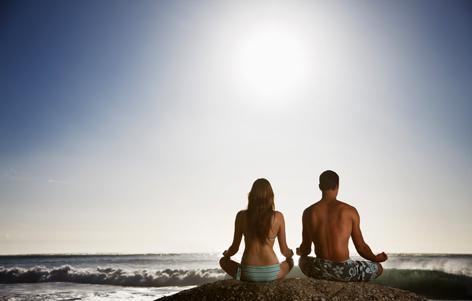 Ein Paar beim Yoga am Strand