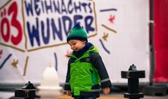 Kind spielt vor der Ö3-Wunderhütte