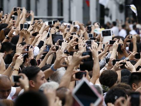 Besucher entlang der Straße fotografieren den Papst mit ihren Handies