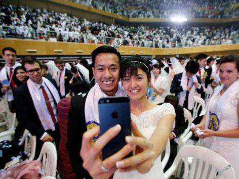 Ein Paar macht ein Selfie bei der Massenhochzeit der Vereinigungsbewegung in Südkorea