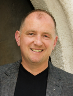 Pfarrer Wolfgang Schnölzer lächelnd unter einem Torbogen