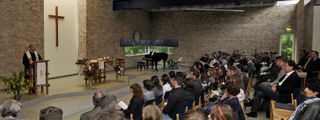 Kirche innen, während Pfarrer zur Gemeinde spricht