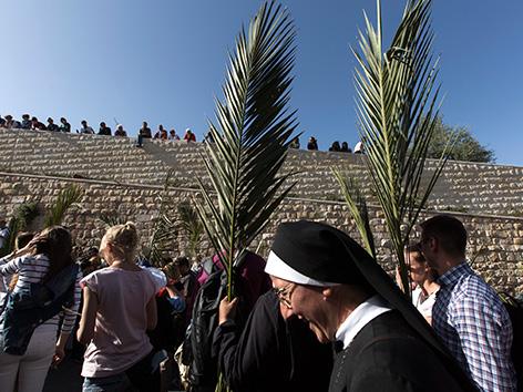 Menschen mit Palmzweigen bei der Palmsonntagsprozession in Jerusalem.