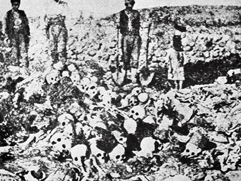 Menschen auf einem Berg menschlicher Gebeine und Schädel