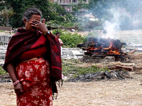 Eine weinende Frau in Bhaktapur nahe Kathmandu steht vor einem Scheiterhaufen nach dem Erdbeben in Nepal