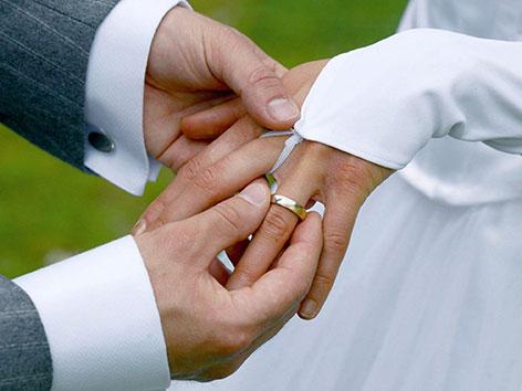 Ein Paar steckt sich Eheringe an die Finger