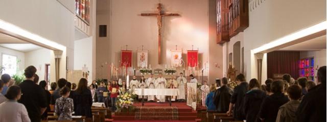 Kirchentotale innen während eines Gottesdienstes mit großem Kreuz an der Wand vor dem Altar