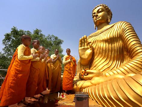 Junge buddhistische Mönche beten zu Vesakh vor einer Buddha-Statue