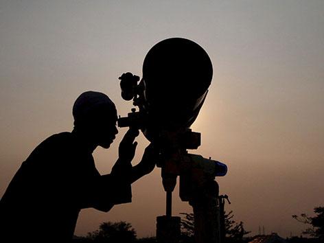 Ein Mann schaut durch ein Fernrohr um für den Beginn des muslimischen Fastenmonats Ramadan die Mondsichel nach Neumond zu entdecken