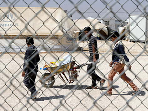 Jugendliche führen in einem Flüchtlingslager in Jordanien  eine Scheibtruhe mit Ramadan-Utensilien