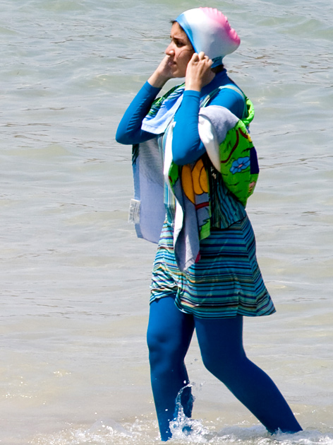 Junge Frau im Meer, mit buntem Burkini bekleidet