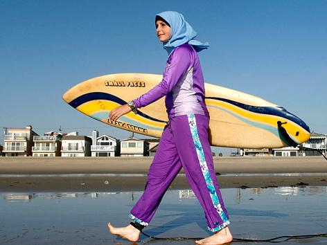 Junge Frau mit Surfbrett in Burkini an einem kalifornischen Strand