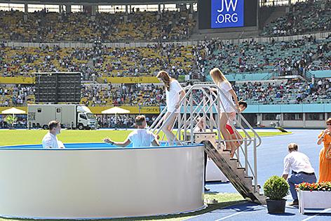 Frauen steigen in den Pool, um sich taufen zu lassen - beim Jehovas-Zeugen-Kongress