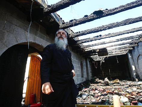Geistlicher in den Trümmern der durch einen Brandanschlag verwüsteten Brotvermehrungskirche in Tabgha, Israel