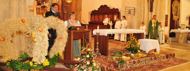 Pfarrer und Gemeindemitglieder im Gottesdienst mit ihren Erntegaben um den Altar