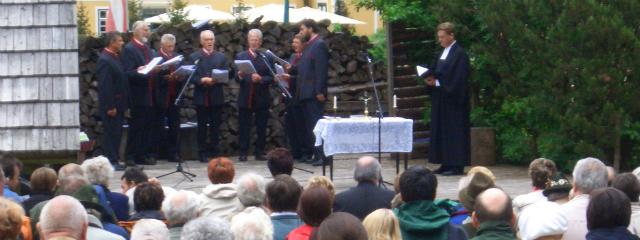 Freiluftgottesdienst mit Altar, Pfarrer, Musikern und der festlich gekleideten Gemeinde