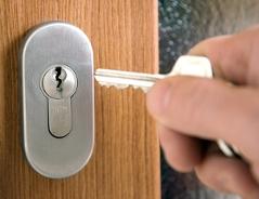Eine Hand öffnet mit einem Schlüssel ein Türschloss