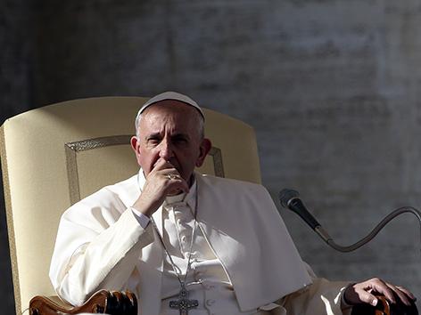 Papst Franziskus verdeckt mit seiner Hand Kinn und Mund