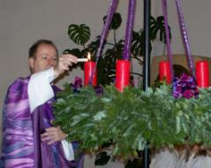 Pfarrer Werner Grad entzündet die erste Kerze am Adventkranz