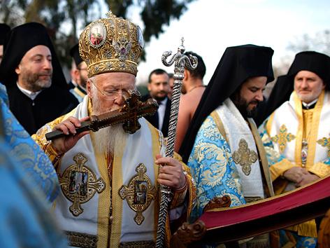 Der Ökumenische Patriarch von Konstantinopel, Bartholomaios I., küsst ein Kreuz anlässlich der Epiphaniasfeiern am Goldenen Horn in Istanbul