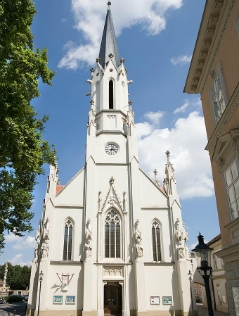die weiße gotische Pfarrkirche Hietzing in Wien von außen im Sonnenschein