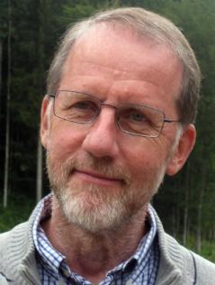 Pfarrer Johannes Kittler lächelnd vor Bäumen