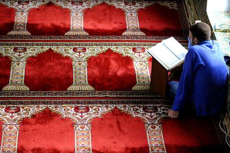 Mann liest in einer Moschee auf einem Teppich